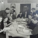"""Служащие совхоза """"Россь"""" в библиотеке, позирование для стенда Всесоюзной сельскохозяйственной выставки, 1949 год, (вторая слева за столом Янина Романчук)"""